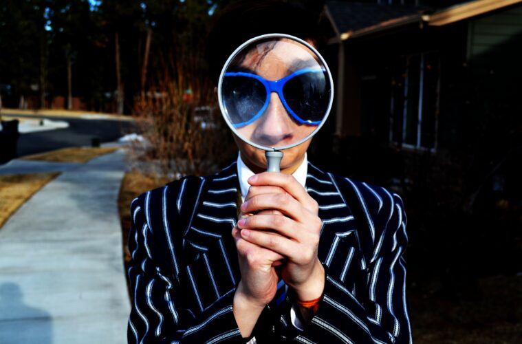 A person holding a magnifying glass.